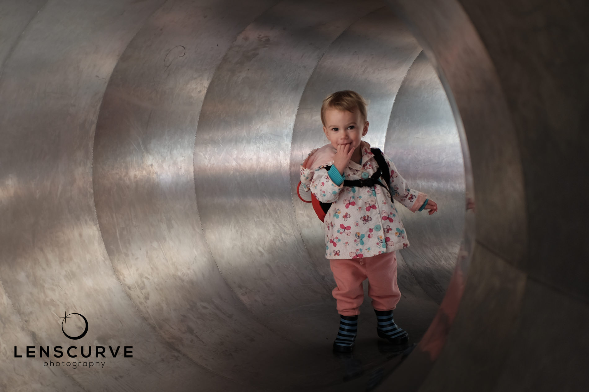 Photograph of a smiling toddler in a metal tunnel in a playpark