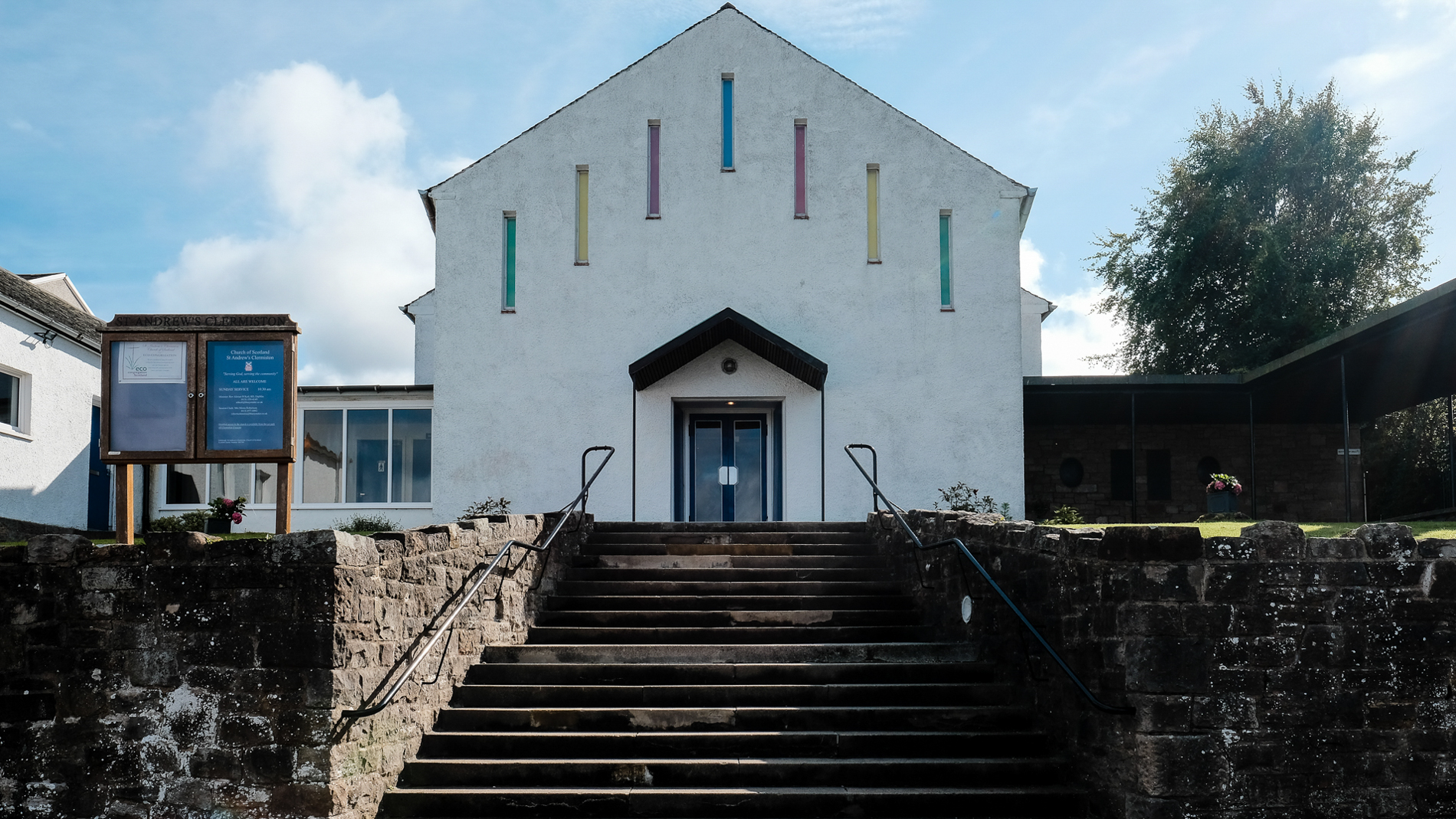 Colour photograph of the front of Saint Andrew's Church in Clermiston, Edinburgh on the day of a wedding