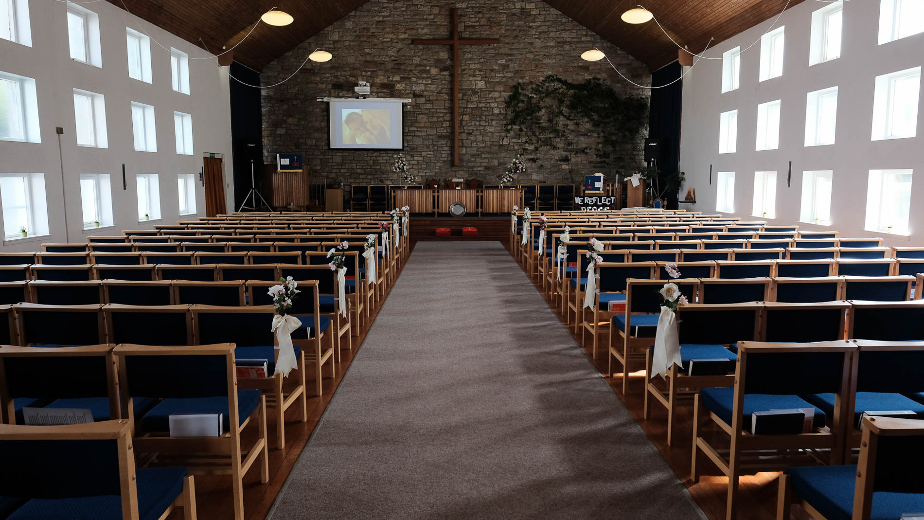 A colour photograph of the interior of Saint Andrew's Church, Clermiston, with wedding flowers and decorations in place before the a wedding