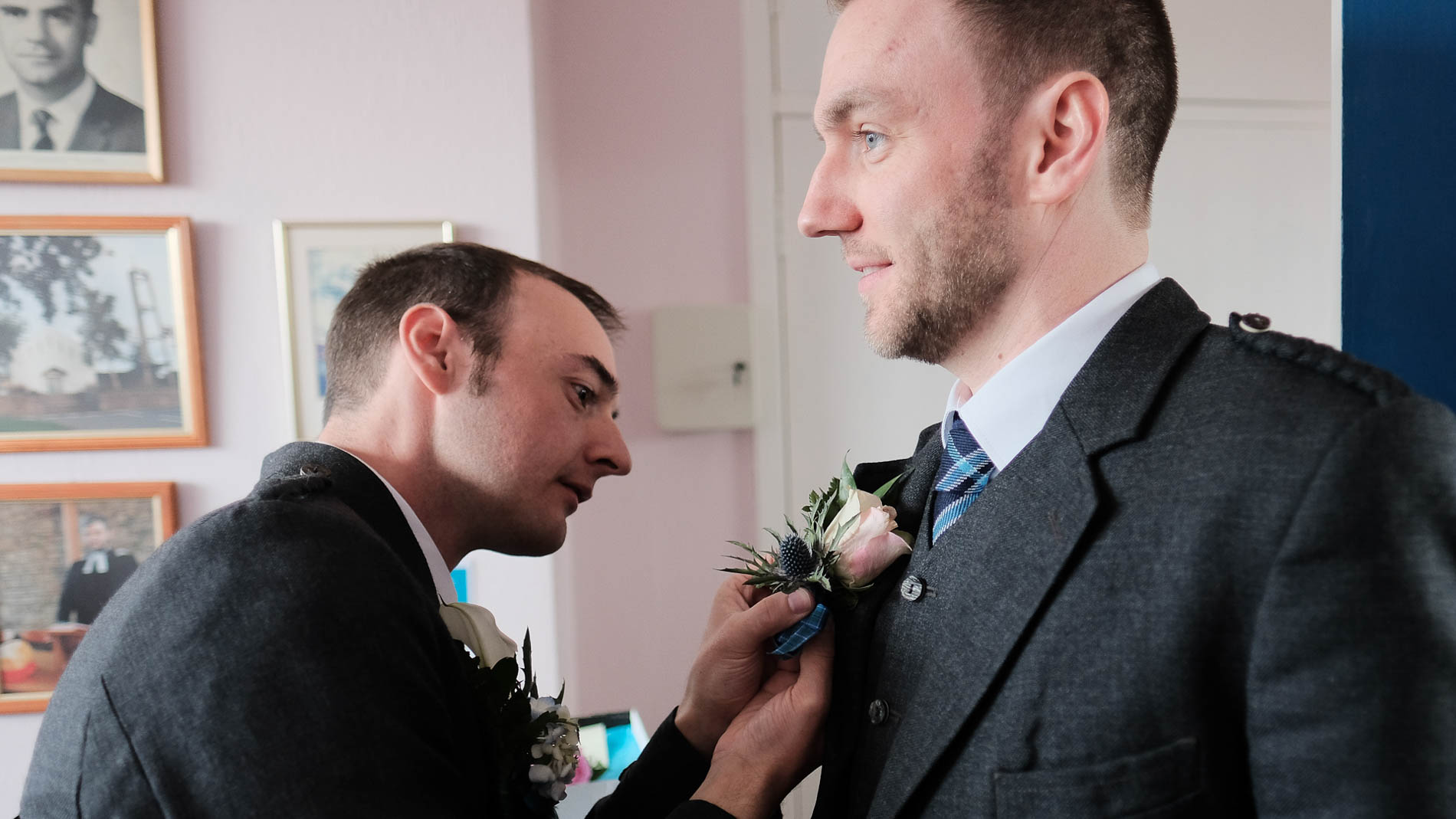 Colour photograph of the groom fixing a buttonhole flower onto the jacket of his best man at his wedding