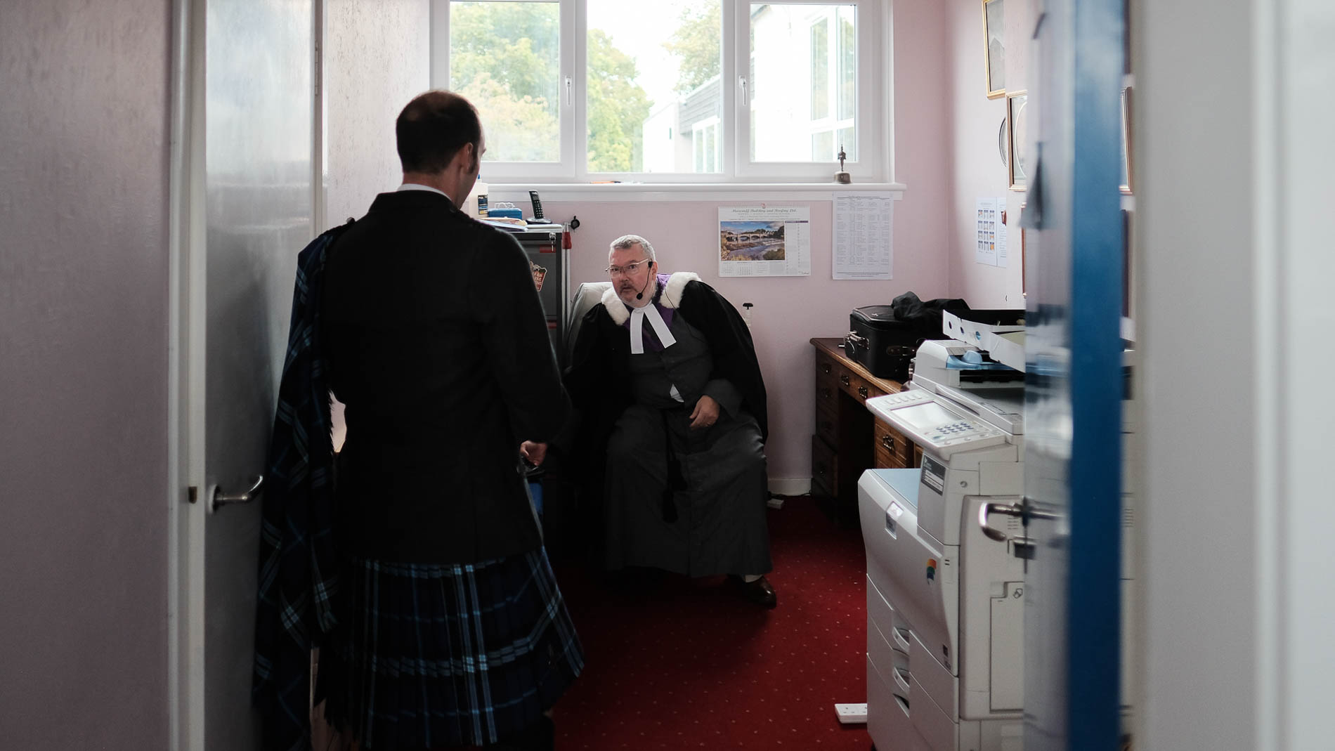 A colour photograph of the groom and minister chatting as they prepare for a wedding at Saint Andrew's Church, Clermiston, Edinburgh