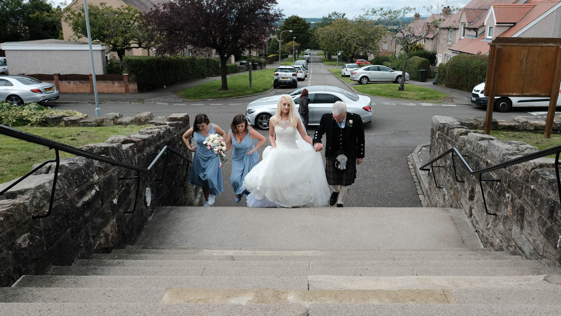 Colour photograph of the bridal party and father of the bride arriving at her wedding at St. Andrew's, Clermiston, Edinburgh