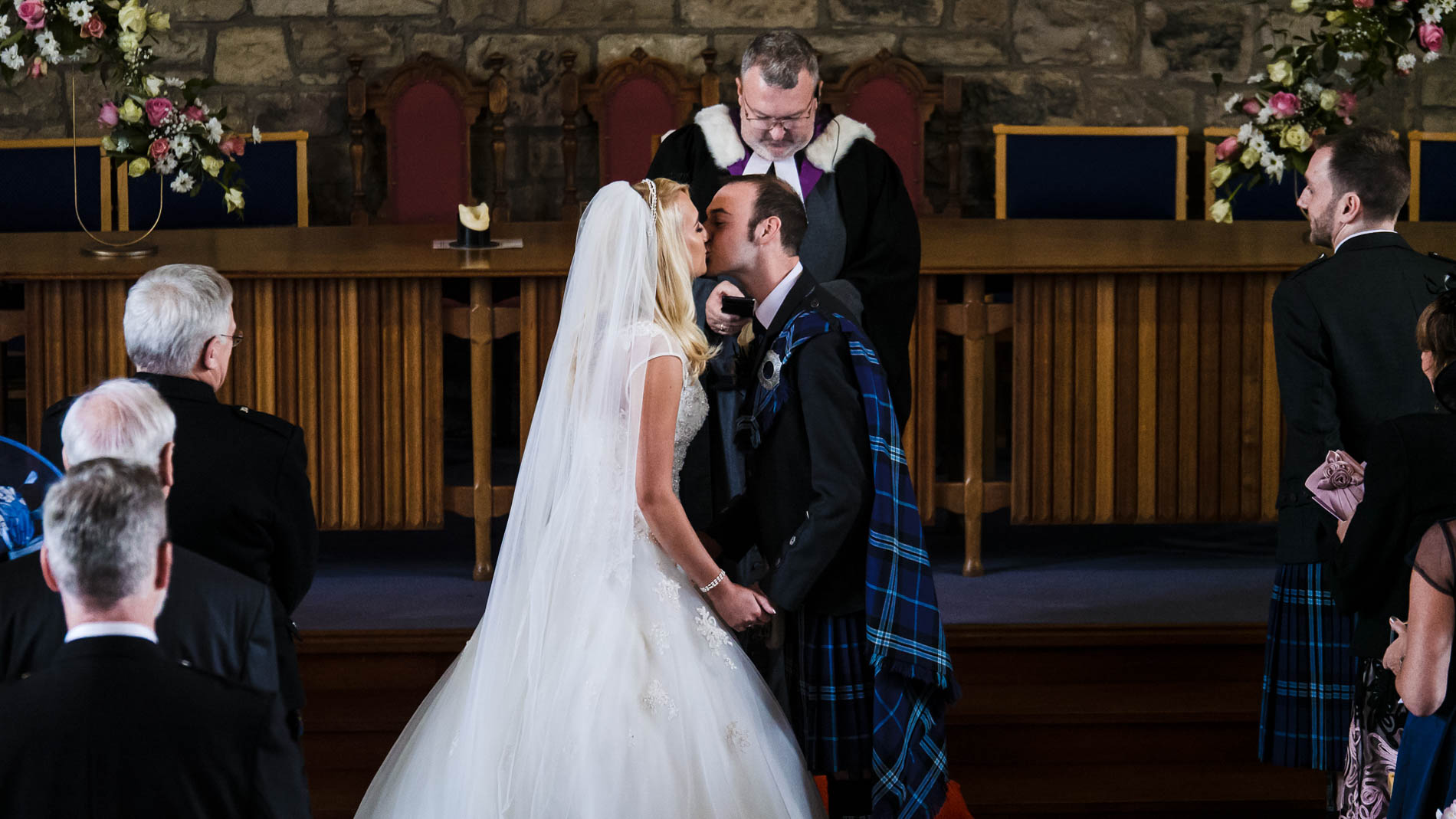 A colour photograph of the bride and groom having their first kiss at the altar of Saint Andrew's Church, Clermiston