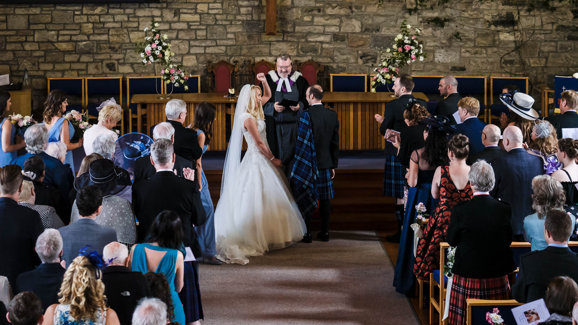 A colour photograph of the bride punching the air in joy at the altar of Saint Andrew's Church, Clermiston