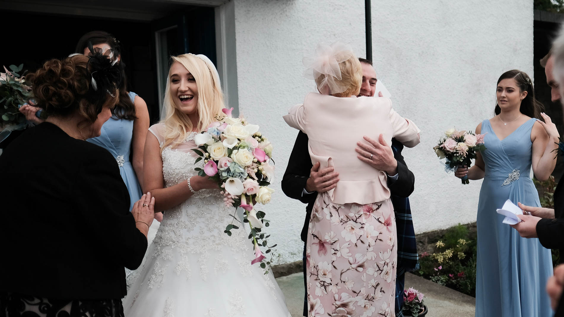 a colour photograph of a bride and groom being congratulated by their families outside a church