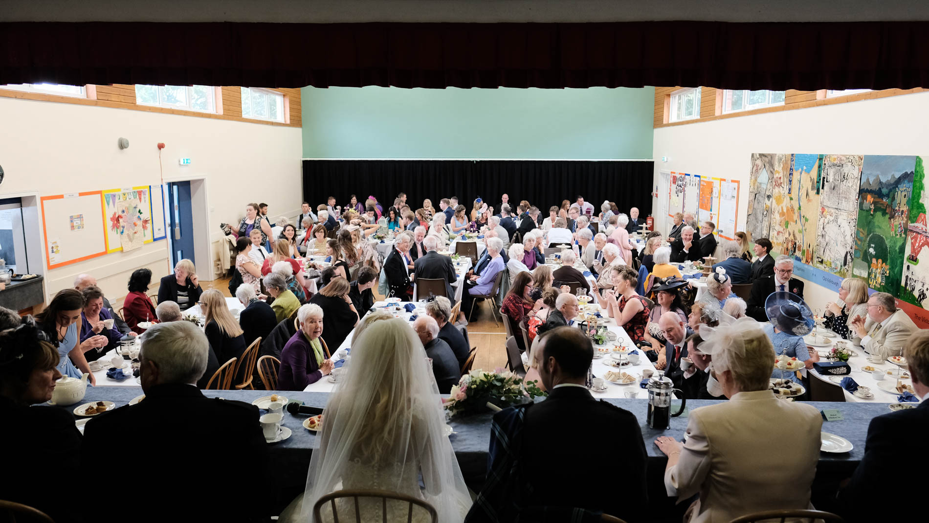 A colour photograph of the church congregation celebrating during an afternoon tea at a wedding at Saint Andrew's Church, Clermiston