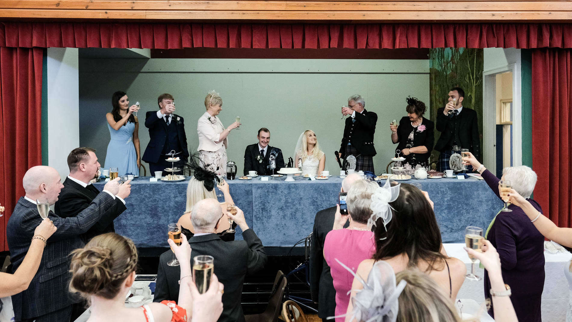 A colour photograph of the bridal party and wedding guests toasting the bride and groom during a wedding reception at Saint Andrew's Church, Clermiston, Edinburgh