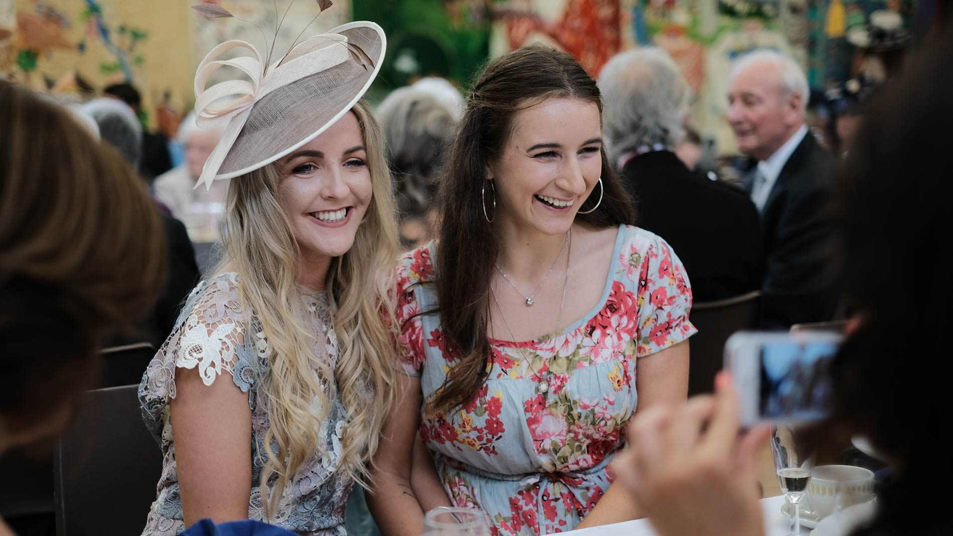 A colour photograph of guests smiling during a wedding reception at Saint Andrew's Church, Clermiston, Edinburgh