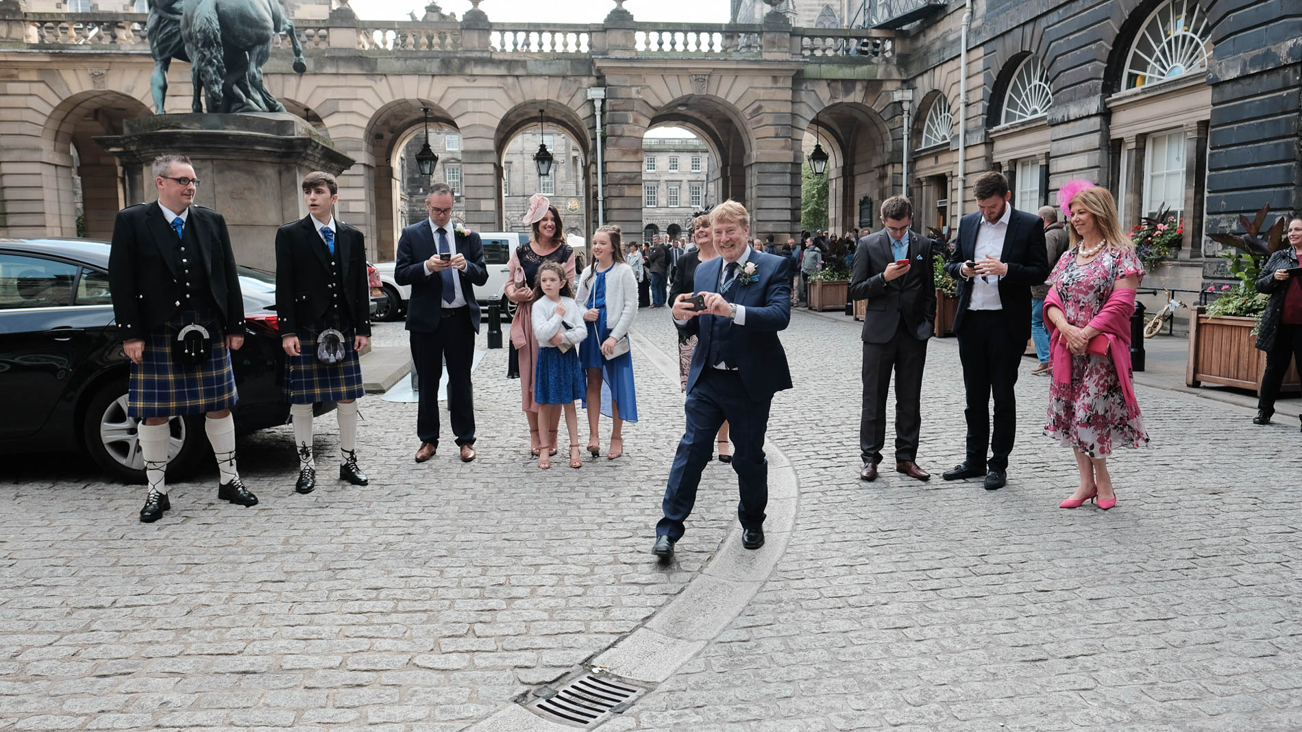 colour photograph of the father of the groom photographing the bride and groom as they arrive outside Edinburgh City Chambers