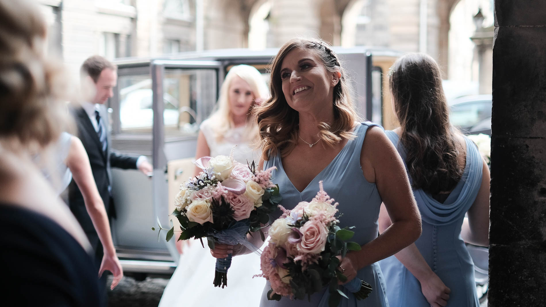 Colour photograph of a bridesmaid carry bouquets of flowers during a wedding at Edinburgh City Chambers