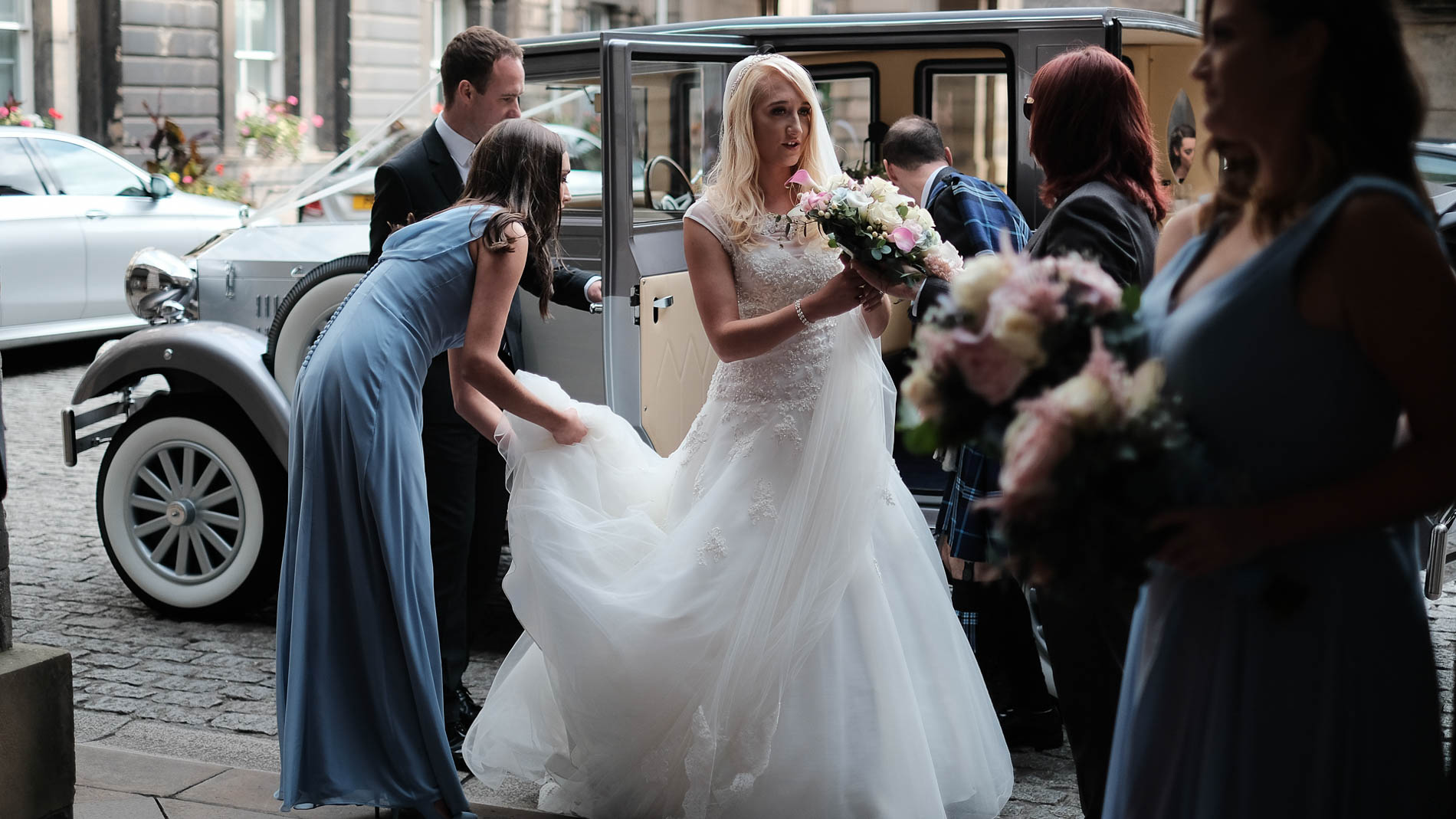 A colour photograph of bridesmaids adjusting the bride's dress as she exits her wedding car
