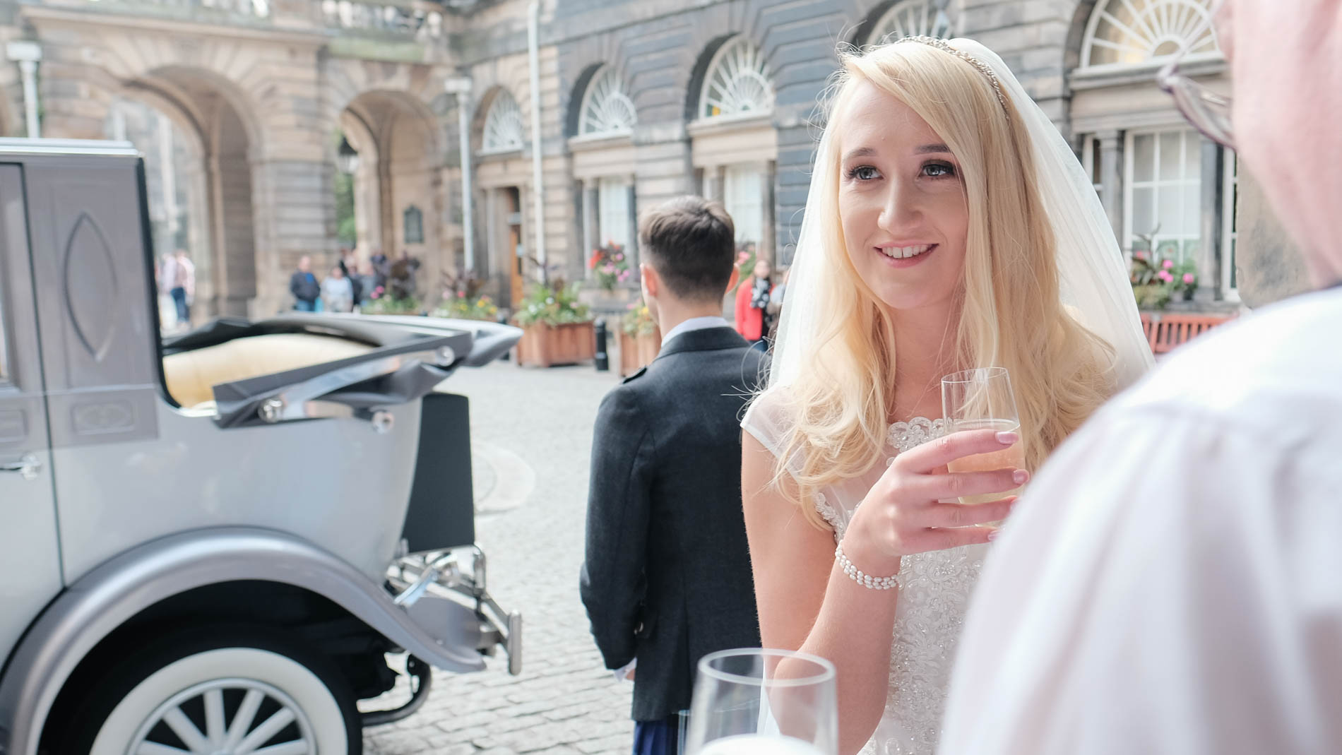 A colour photograph of a bride with a glass of champagne outside Edinburgh City Chambers