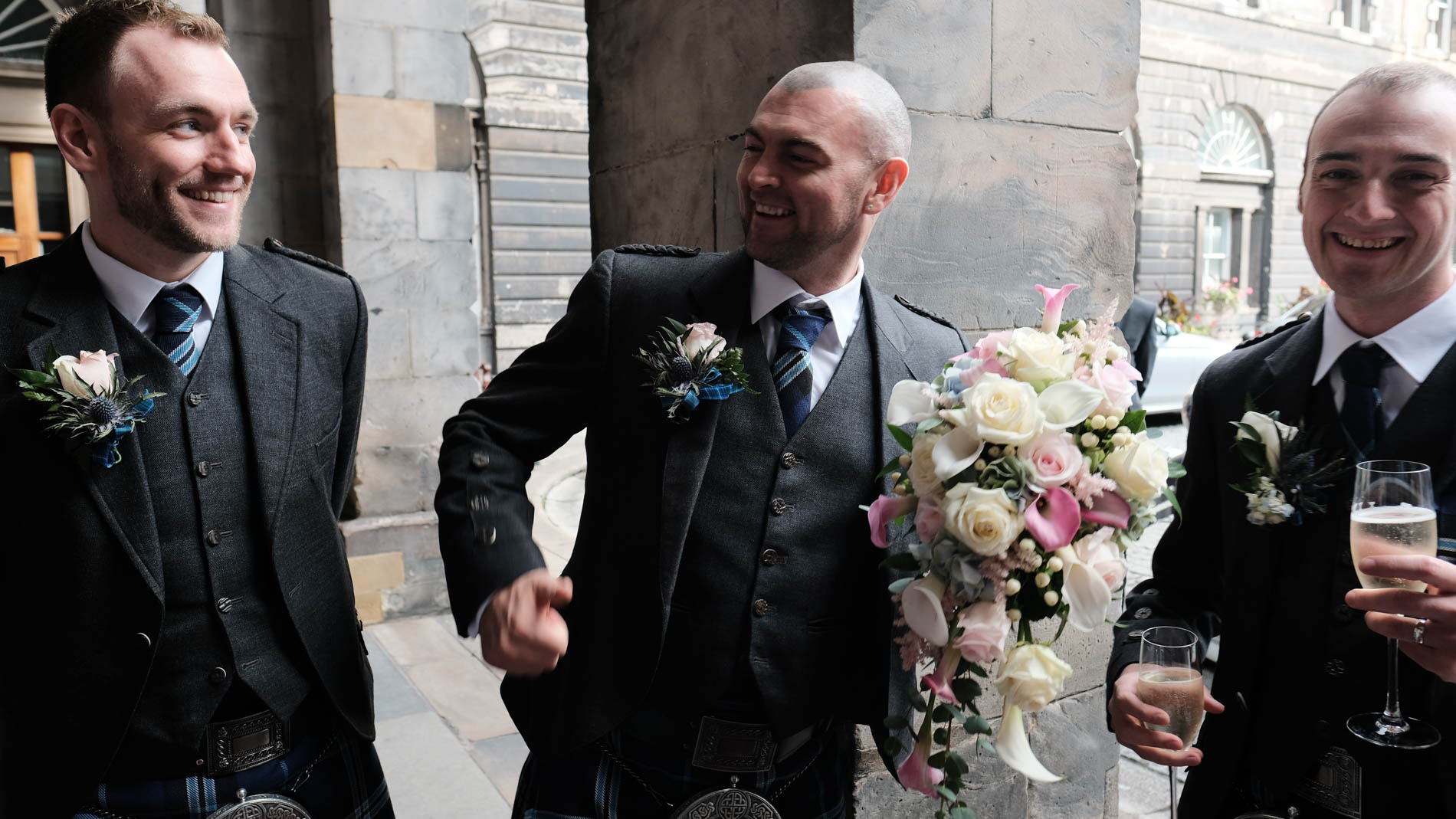 A colour photograph of the groom and his groomsmen laughing outside Edinburgh City Chambers