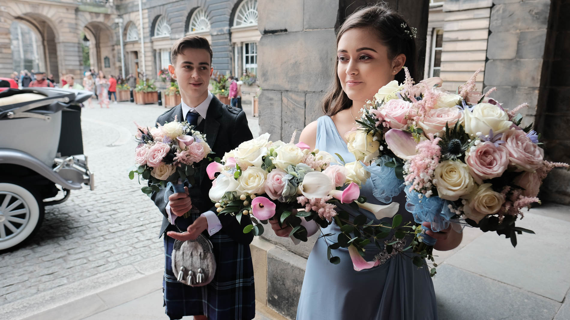 Colour photograph of an usher and a bridesmaid hiding flowers outside Edinburgh City Chambers