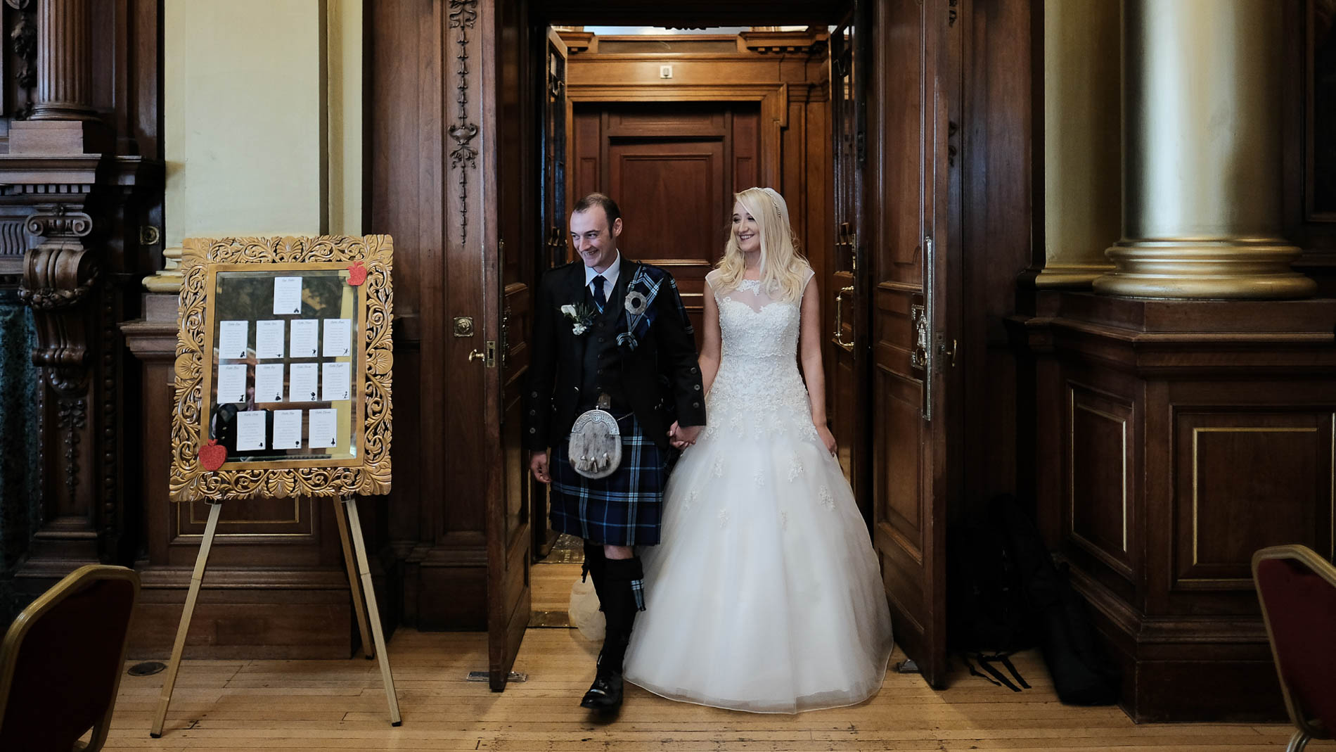 A colour photograph of the bride and groom walking in to their wedding reception in the Debating Chamber, Edinburgh City Chambers
