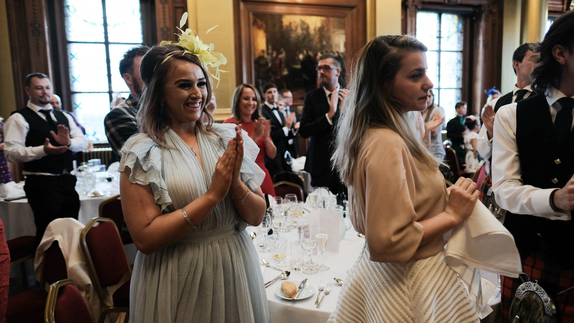 A colour photograph of wedding guests clapping and smiling during a wedding reception in Edinburgh City Chambers