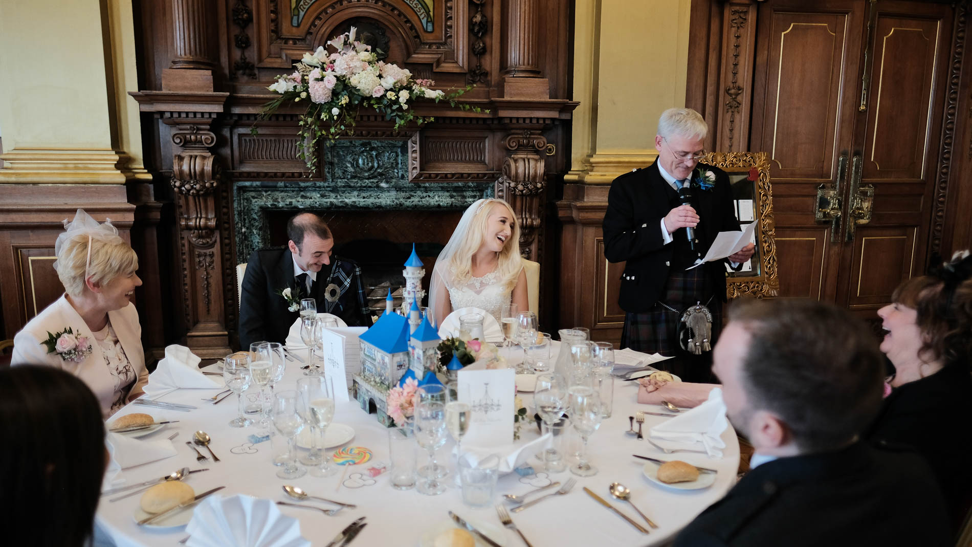 A colour photograph of the father of the bride giving his speech to his daughter at her wedding reception in the Debating Chamber, Edinburgh City Chambers