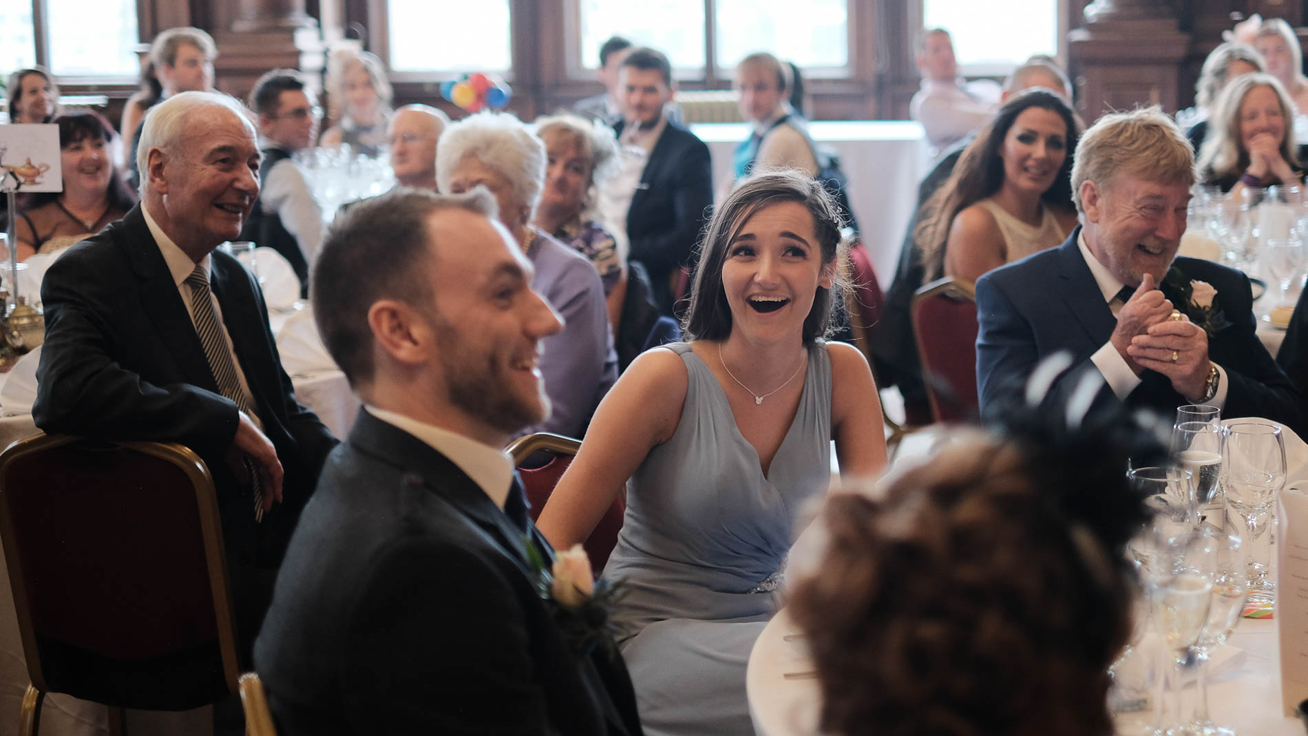A colour photograph of wedding guest laughing during a wedding reception in Edinburgh City Chambers