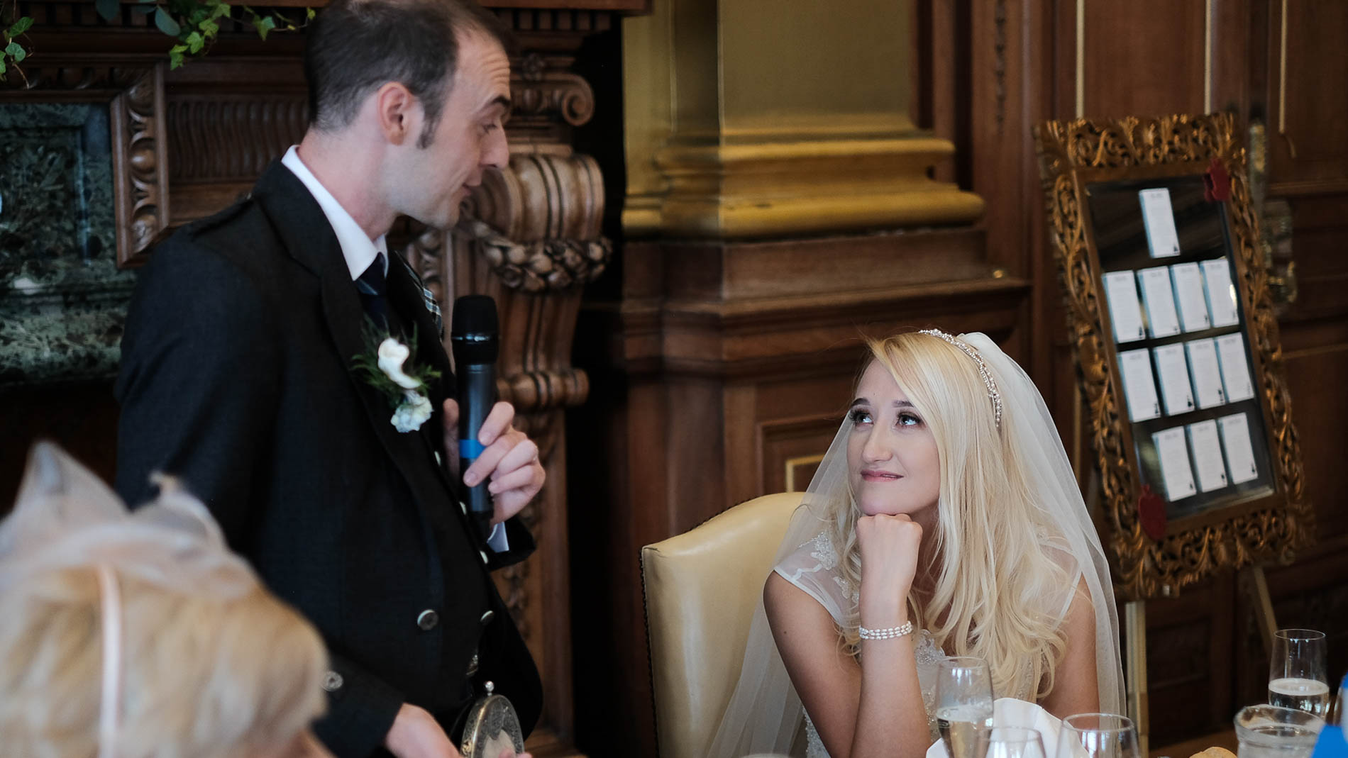 A colour photograph of the bride and groom sharing a tender moment as the groom gives his speech during their wedding reception in Edinburgh City Chambers