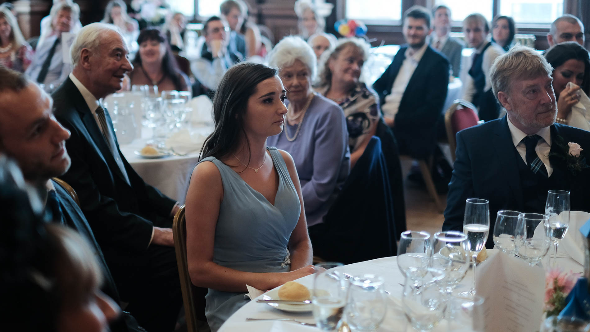 A colour photograph of wedding guests looking emotional during a wedding speech at Edinburgh City Chambers