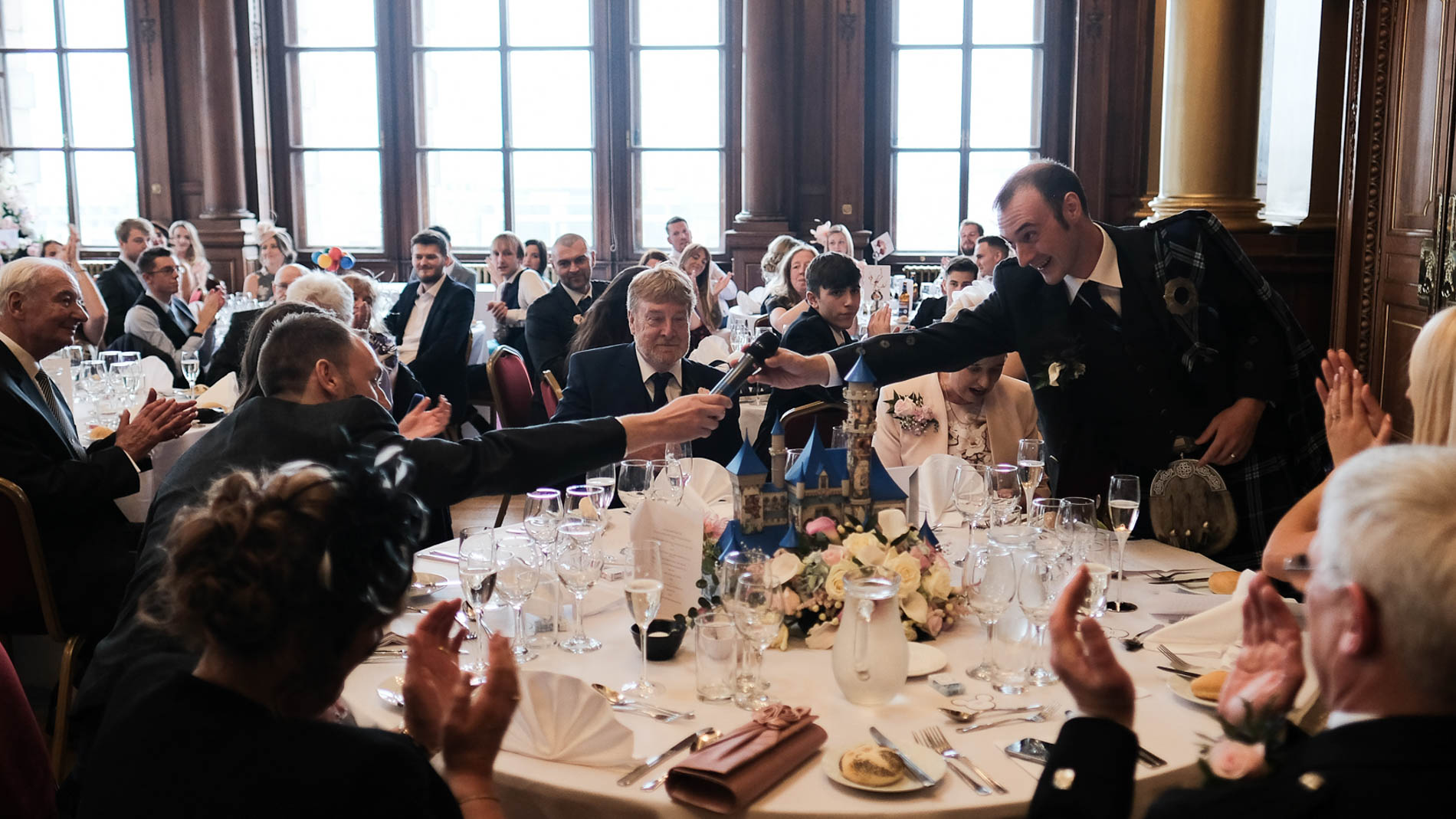 A colour photograph of the bridegroom passing the microphone to his best man during his wedding reception in Edinburgh City Chambers