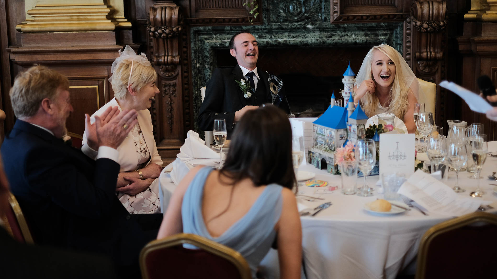 A colour photograph of the bride and groom laughing during the best man's speech