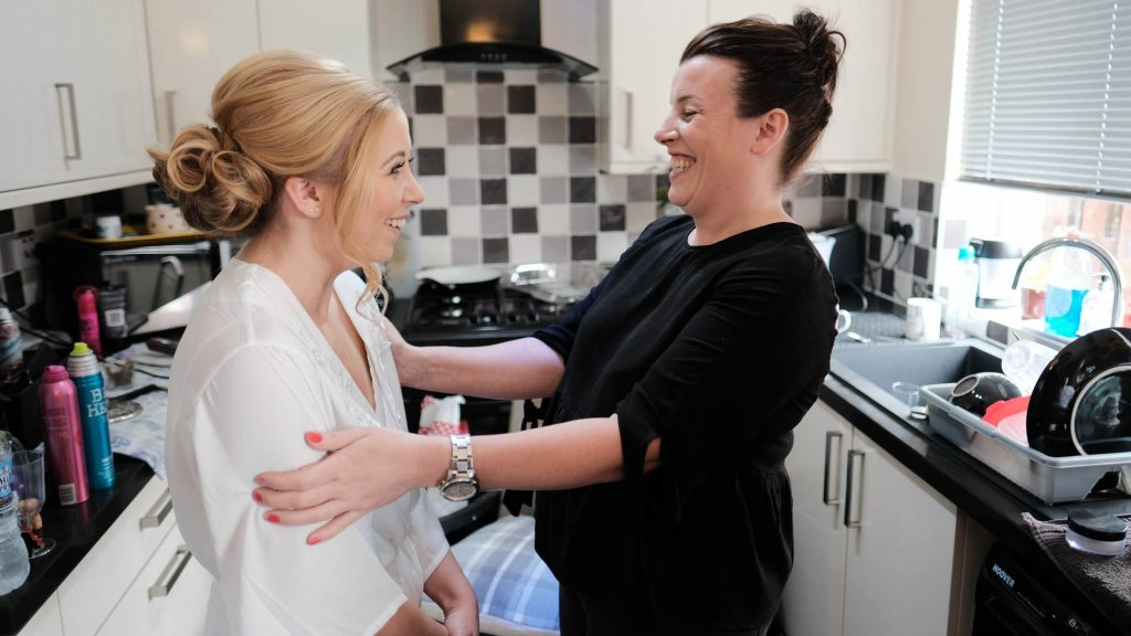 colour photograph of a bride smiling at her hairdresser as she gets ready for her wedding day