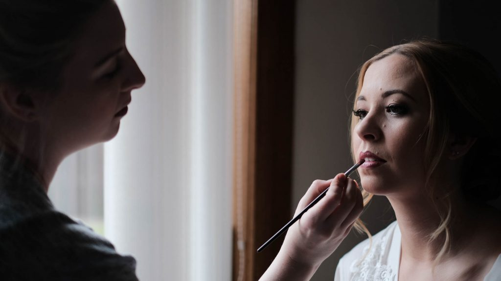 colour photograph of a bride having her makeup applied for her wedding