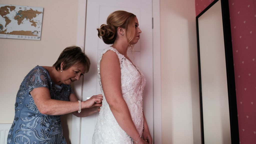 colour photograph of a bride in her wedding dress getting ready for her wedding