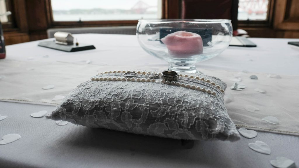 colour photograph of wedding rings on a cushion before a wedding