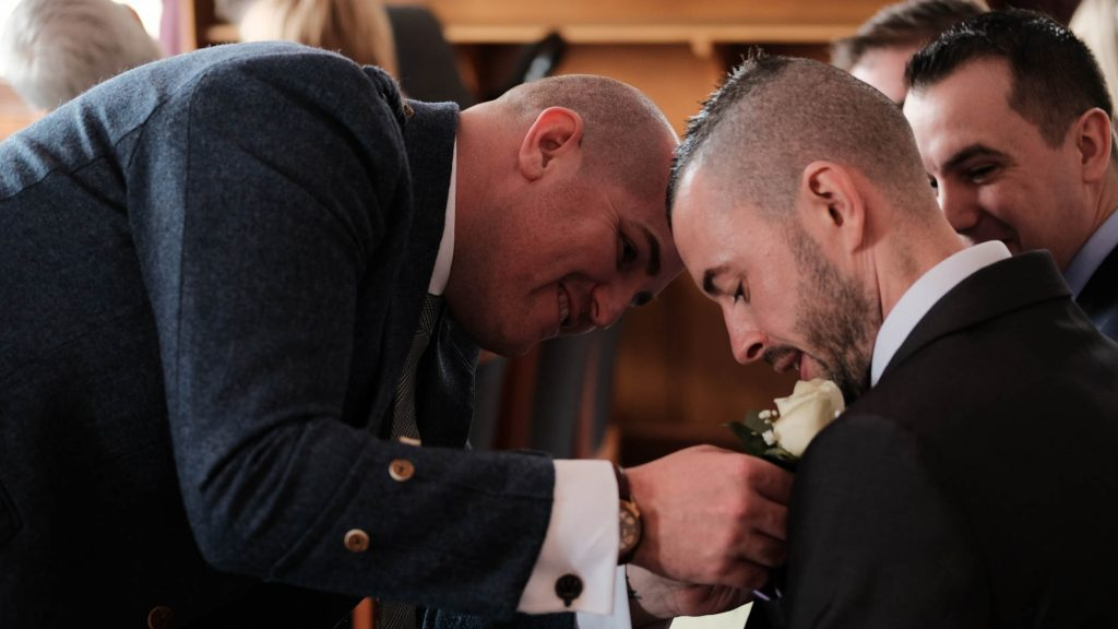 colour photograph a bridegroom having his buttonhole flower fixed before his wedding starts