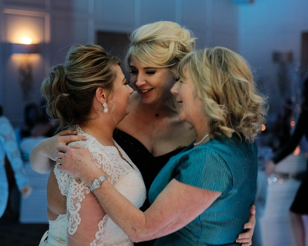 A colour photograph of a bride, her mother and her sister hugging on the dance floor during her wedding