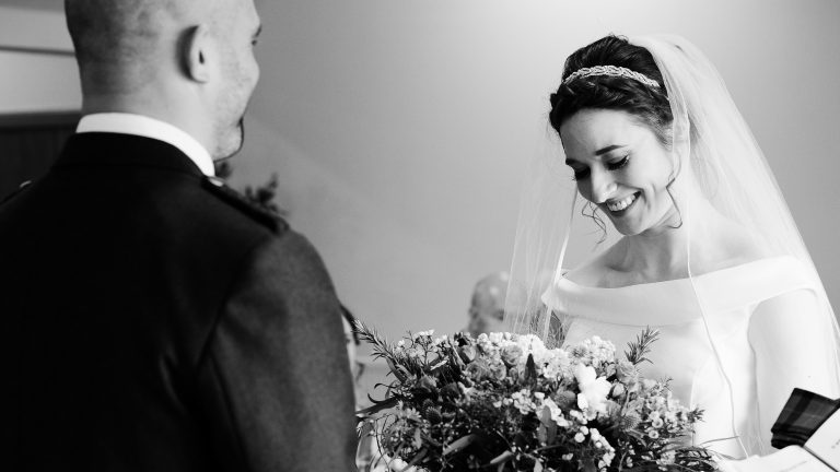monochrome image of a bride smiling during her wedding ceremony