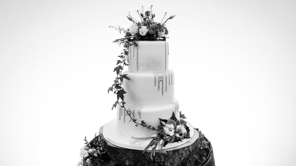 Monochrome image of a wedding cake placed on a wooden whisky barrel