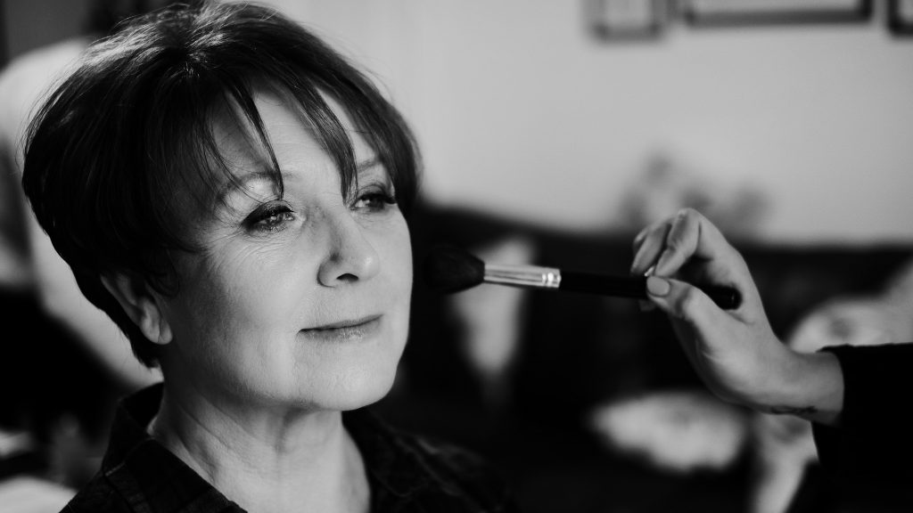 Monochrome photograph of the mother of the bride having her make up done for her daughter's wedding