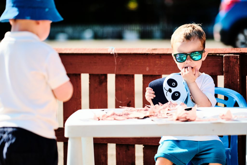 colour photograph of a boy doing crafts outside on a table