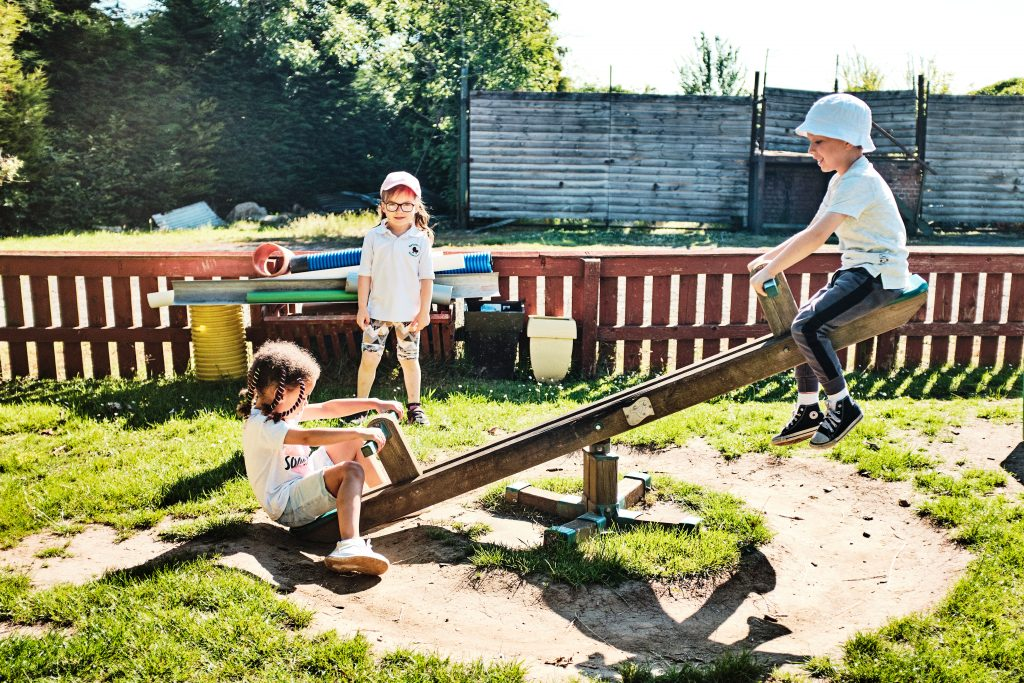colour photograph of a children playing on a seesaw