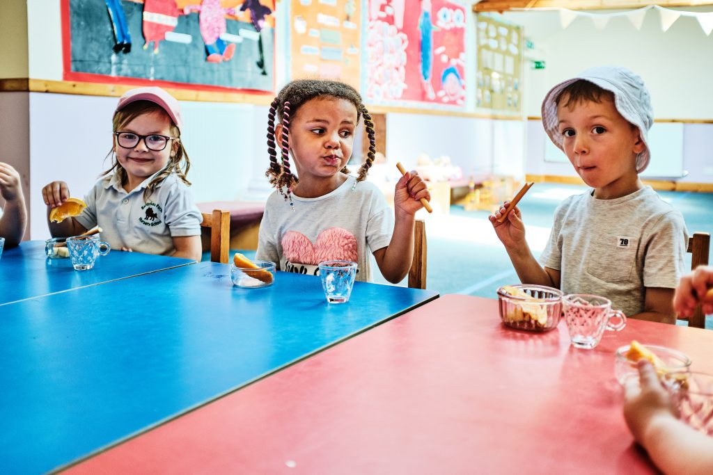 colour photograph of children eating a table