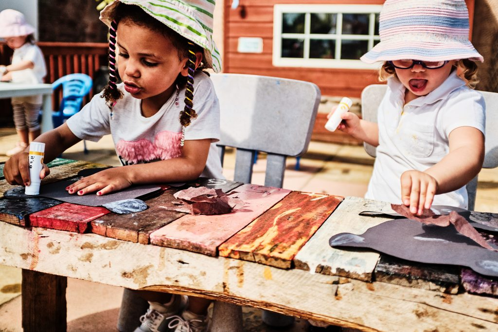 colour photograph of two girls doing crafts