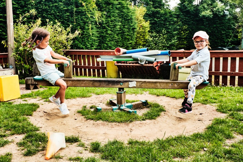 colour photograph of tow children playing on a seesaw