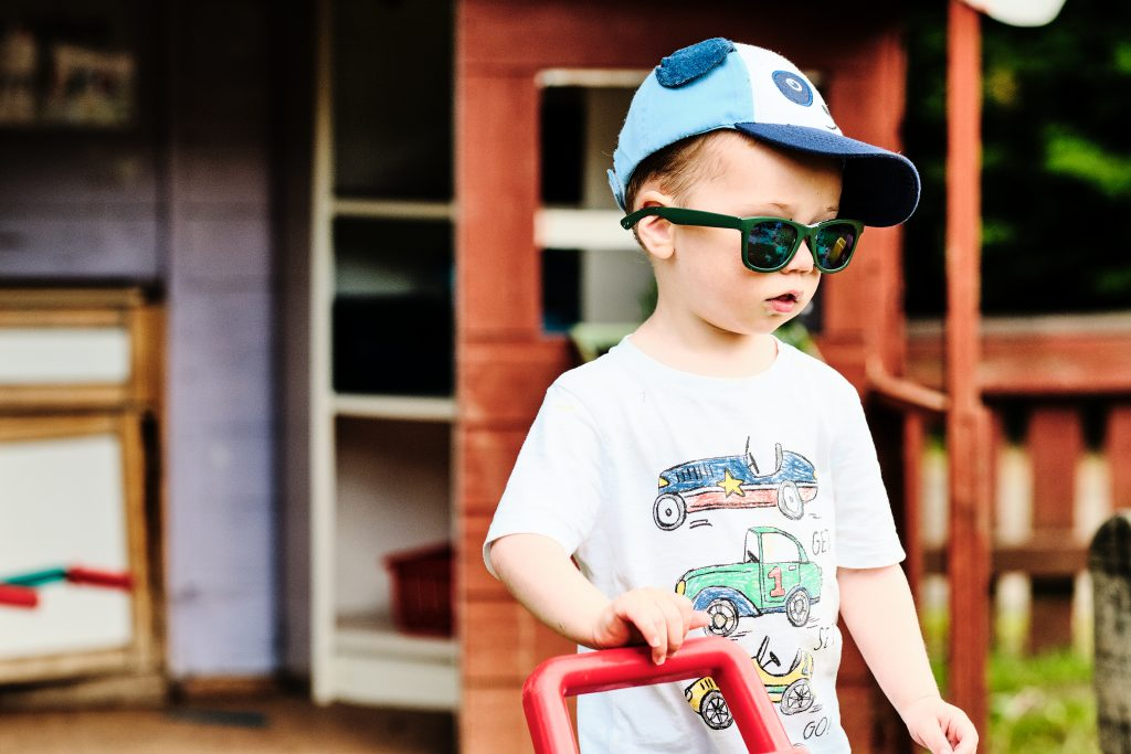 colour photograph of a small boy wearing a hat and sunglasses