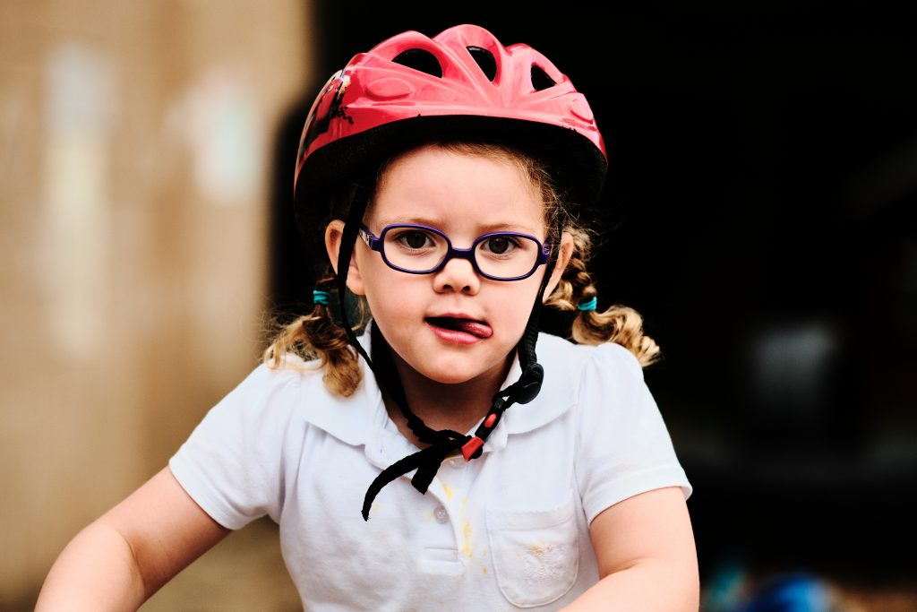 colour photograph of a young girl riding a bike