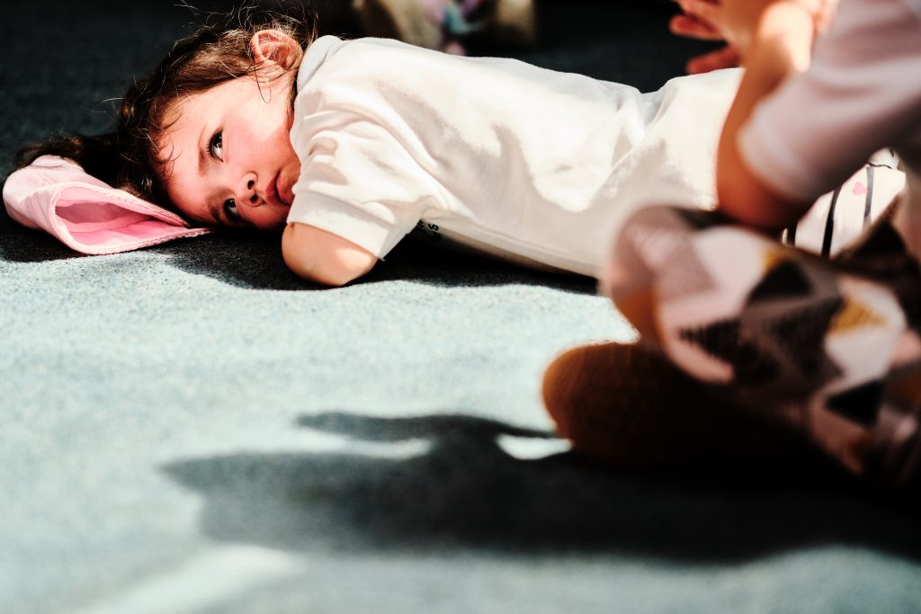 colour photograph of a girl lying on the floor