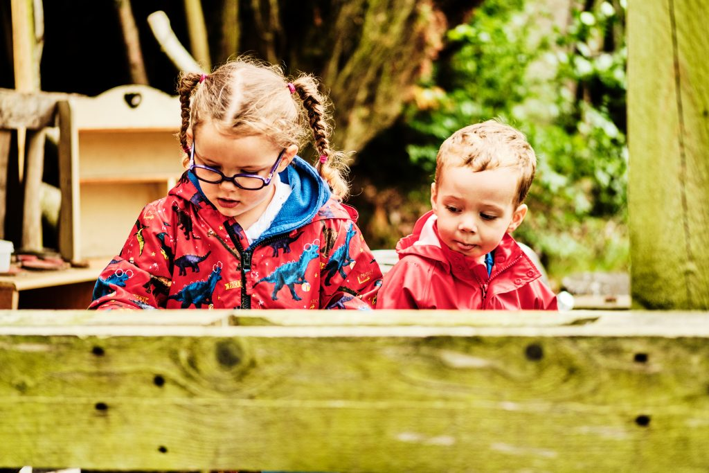 colour photograph of a boy and girl playing outside in a garden