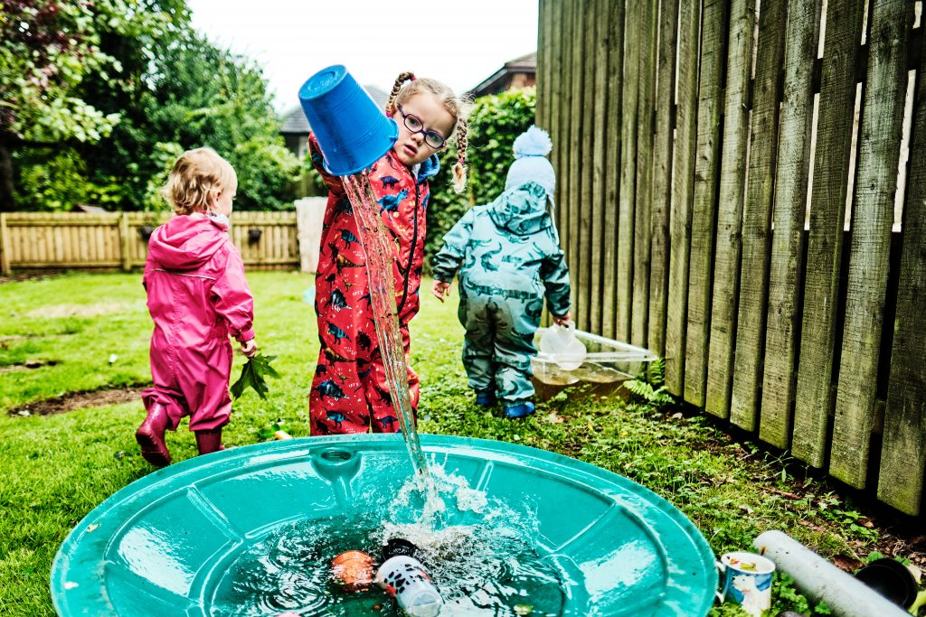 colour photograph of a girl playing with water outside at nursery school