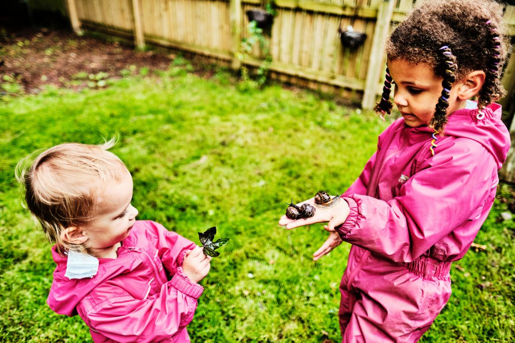 colour photograph of 2 girls with a snail