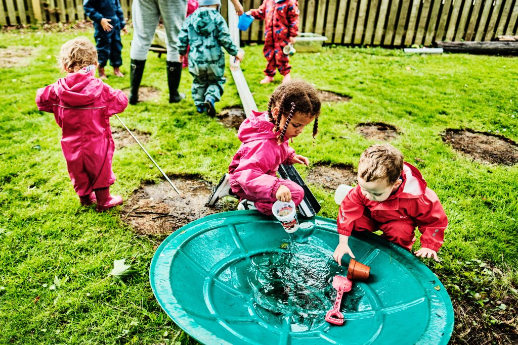 colour photograph of children playing with water outside at nursery school