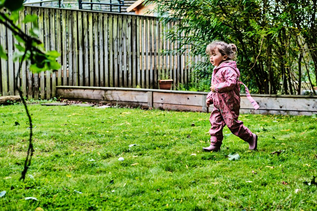 colour photograph of a toddler running in a garden