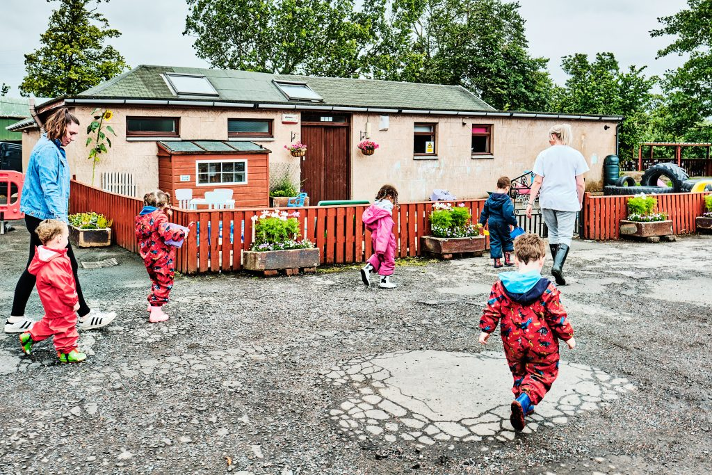 colour photograph of a nursery class walking back to their school