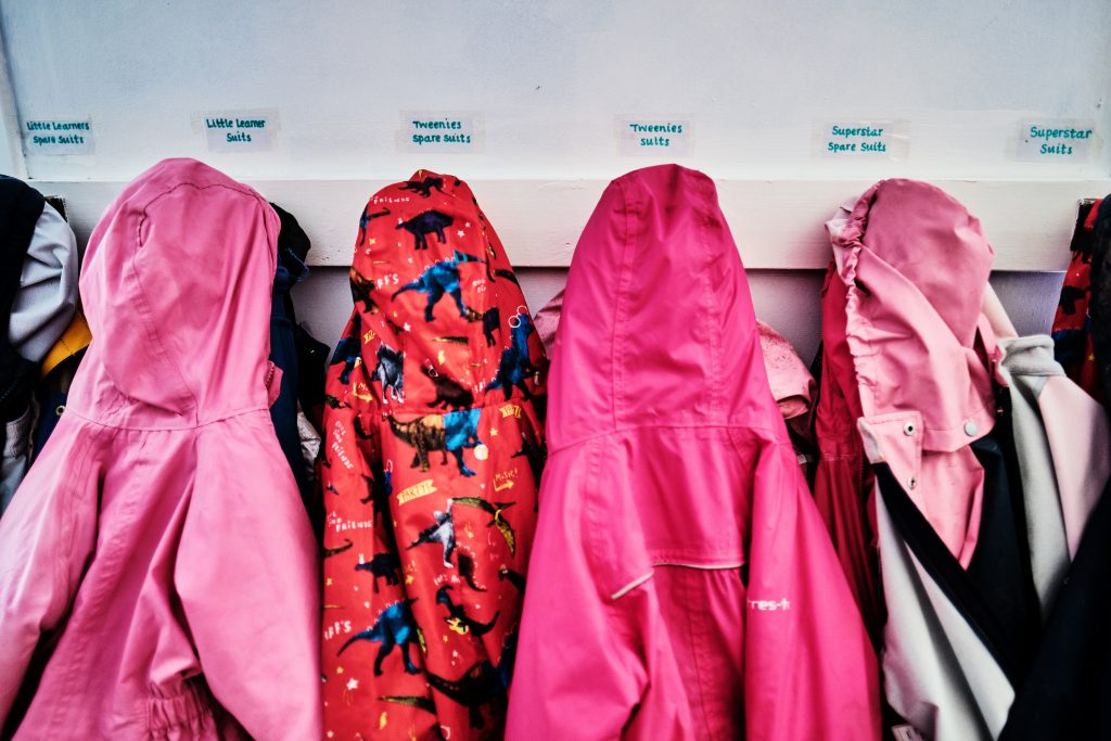 colour photograph of children's overalls having up at a nursery school